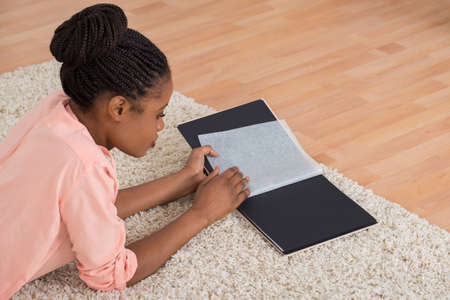 people watching: Young African Woman Looking Blank Photo Album In Living Room Stock Photo