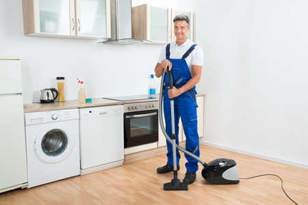 Full Length Portrait Of Male Janitor Cleaning Floor With Vacuum Cleaner In  Kitchen Stock Photo