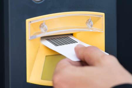 pagando: Primer plano de la mano de una persona insertando el boleto de estacionamiento en la ranura Foto de archivo