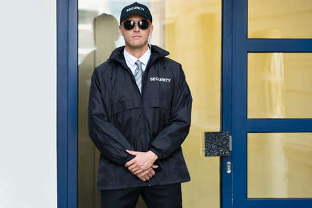 Young Male Security Guard Standing At The Entrance Stock Photo