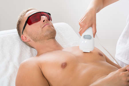 Weiblich Kosmetikerin, die Haarentfernung mit Laser On Mannes Brust