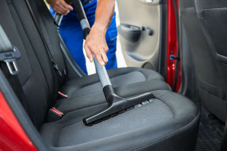 Handyman vacuuming car back seat with vacuum cleaner