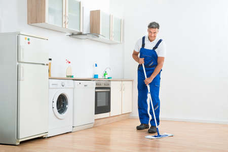 mopping: Full length of male worker mopping floor in kitchen at home
