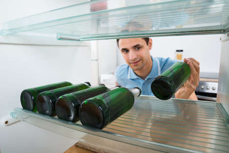 liquors: Smiling young man removing beer bottle from refrigerator at home