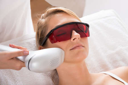 laser: Closeup of young woman undergoing laser treatment at salon Stock Photo