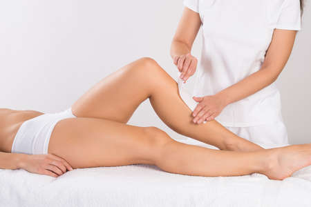 salon: Midsection of beautician waxing womans leg at salon