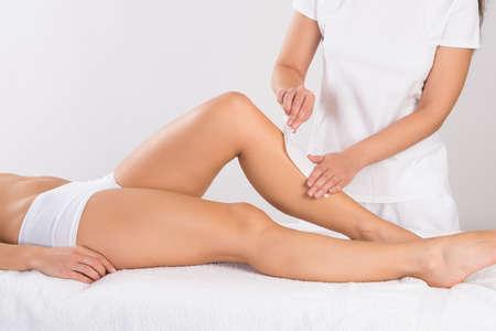 depilacion con cera: Sección media de esteticista depilación pierna de la mujer en el salón