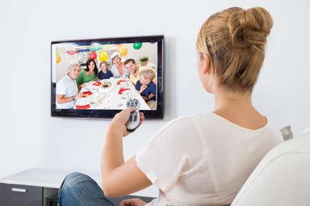 Mujer joven que ve la televisión mientras está sentado en el sofá en la sala de estar