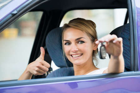 thumb keys: Portrait of happy young woman gesturing thumbs up while holding key in car