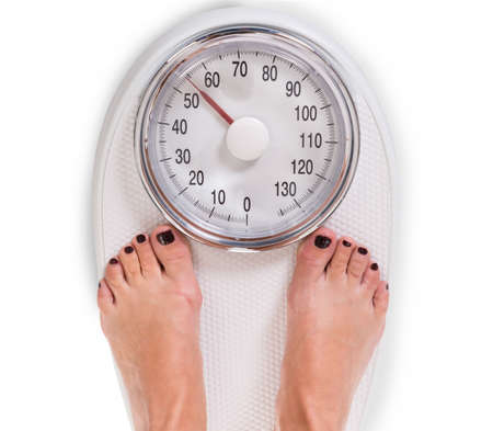 High angle view of woman's legs on weighing scale over white background