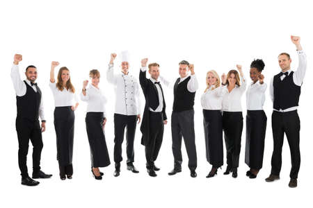 Full length portrait of happy restaurant staff celebrating success against white background