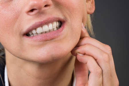 ache: Cropped image of young businesswoman suffering from tooth ache over gray background