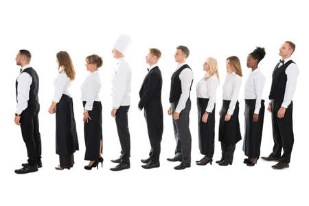 staff: Full length side view of restaurant staff standing in line against white background Stock Photo