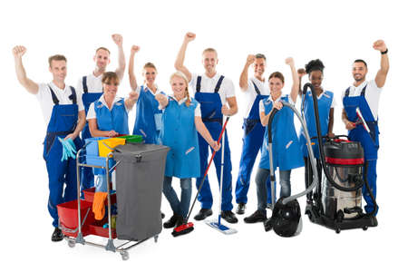 Portrait of happy multiethnic janitors with arms raised holding cleaning equipment against white background Stock Photo