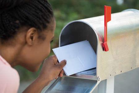 メールボックスに手紙を入れて女性をクローズ アップ