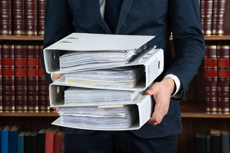 lawyer in court: Midsection of male lawyer carrying stack of ring binders in courtroom