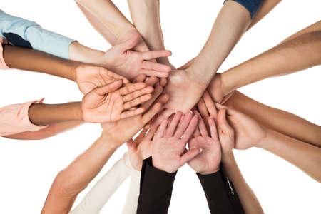 piling: Directly below shot of creative business team piling hands against white background