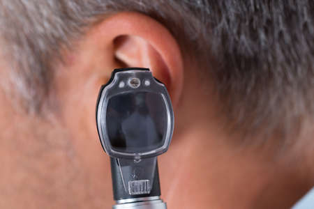 by ear: Close-up Of Doctor Looking Through Otoscope In Mans Ear Stock Photo