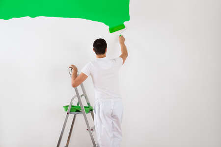 Rear view of young man painting wall with green paint roller at home