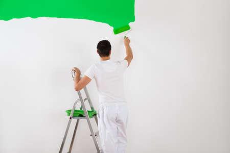 hombre pintando: Vista posterior de la pared de pintura joven hombre con el rodillo de pintura verde en el país