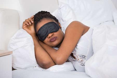 eye mask: African Woman Wearing Eyemask While Sleeping On Bed