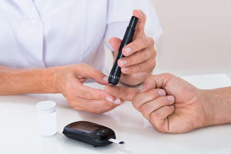 blood sugar: Close-up Of Doctor Measuring Sugar Reading Of Patient With Glucometer