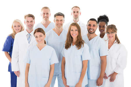 Portrait of happy multiethnic medical team standing against white background