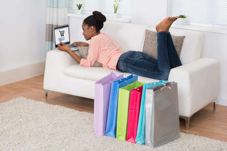 shopping basket: Young African Woman Lying On Sofa Shopping Online On Laptop