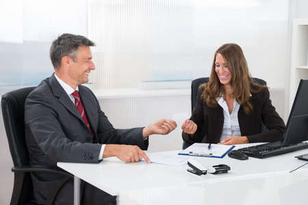 exchanging: Two Businesspeople Exchanging Blank Visiting Card At Desk In Office