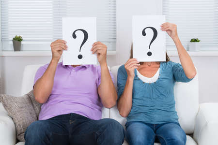 Couple Together Sitting On Sofa Hiding Face With Question Mark Sign Фото со стока