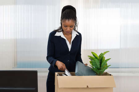 relocating: Sad African Businesswoman Carrying Box With Her Belongings In Office