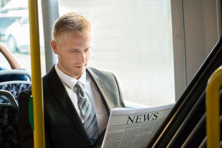 periodicos: El hombre de negocios joven que se sienta en periódico de la lectura de tranvía