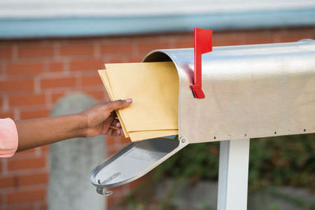 direct marketing: Close-up Of Persons Hand Putting Letters In Mailbox Stock Photo