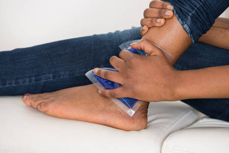 bags in hands: Close-up Of Persons Hand Holding Ice Gel Pack On Ankle Stock Photo