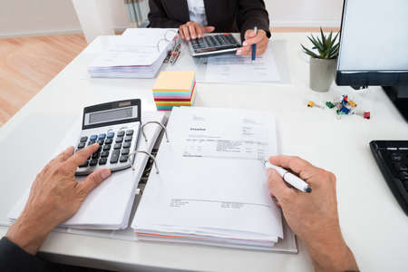 financial statement: Close-up Of Two Businesspeople Calculating Financial Statement At Desk