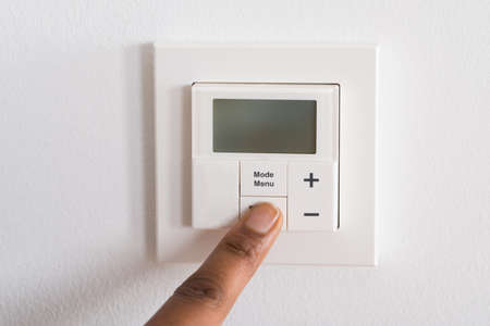 programmable: Close-up Of Persons Finger Adjusting Room Temperature On Digital Thermostat