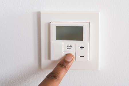 adjusting: Close-up Of Persons Finger Adjusting Room Temperature On Digital Thermostat