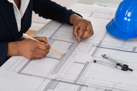 black hands: Close-up Of A Businesswoman Drawing Blueprint At Office Desk Stock Photo