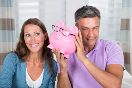 financial planning married: Happy Couple Listening To Sound Of Coins In Piggybank