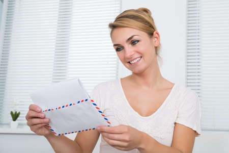 envelop: Happy young woman reading letter while sitting at home