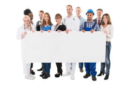 흰색 배경에 대해 빈 빌보드를 들고 다양한 직업을 가진 사람들의 그룹 초상화 스톡 콘텐츠