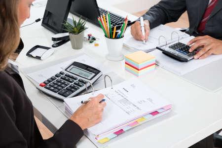 デスクで財務諸表を計算する 2 つのビジネスマンのクローズ アップ