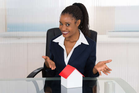 property agent: Smiling Young African Businesswoman Presenting A House Model At Office Desk