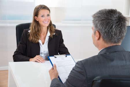 entrevista de trabajo: Gerente maduro entrevistar a un solicitante Mujer En La Oficina Foto de archivo