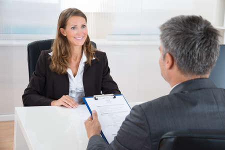 job vacancies: Mature Manager Interviewing A Female Applicant In Office