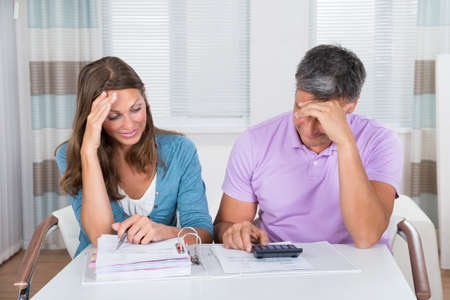 unpaid: Worried Couple Looking At Unpaid Bills At Home