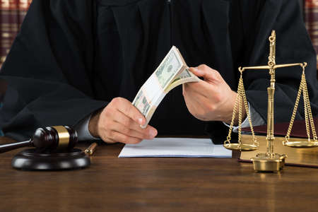 corruption: Midsection of male corrupt judge holding dollar bundle at desk in courtroom Stock Photo