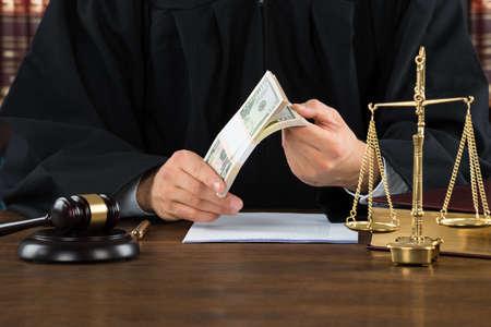corrupcion: Sección media de haz de dólares sosteniendo juez corrupto masculina en el escritorio en sala