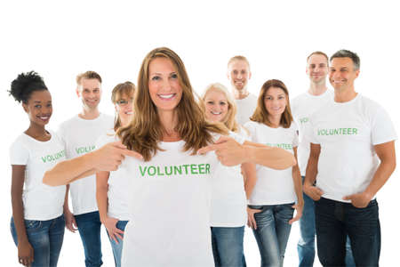 volunteer point: Portrait of happy woman showing volunteer text on tshirt with friends standing over white background Stock Photo