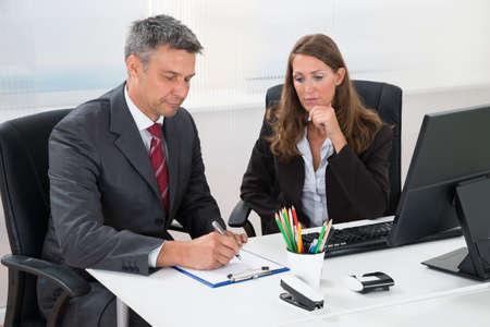 hombre escribiendo: Empresario maduro Escritura En Portapapeles Con Femenino Auxiliar En El Escritorio De Oficina